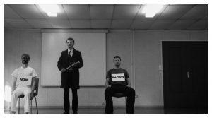 Homme debout entre deux hommes assis avec des pancartes autour du cou